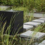 Schwarzer Wasserwürfel und helle Trittplatten im Schwimmteich an der Filterzone