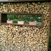 Gestapeltes Holz als Sichtschutz oder dekoratives Gartenelement