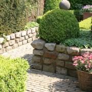 Naturstein-Granit-Mauer als Hochbeet, davor ein Weg als altem Backstein