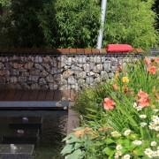 Gabionen als Sitzmauer mit einem Wasserspiel und quadratischen Quellsteinen