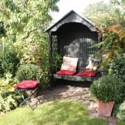 Gemütliche Gartenecke mit überdachter Gartenbank