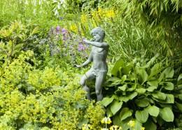 Gartenskulptur zwischen Stauden - Pan als Kupferfigur