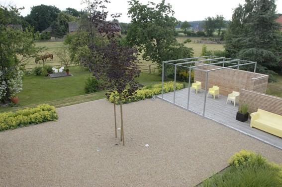 Kiesflächen mit Holzterrasse, Frauenmantel und Sichtschutzwand