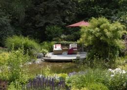 rundes Holzdeck mit Sonnenliegen und Teich mit glasklarem Wasser