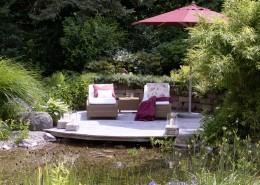 romantisches Holzdeck am Gartenteich mit Natursteinmauer