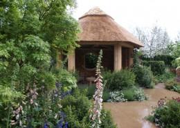 Strohgedeckter Gartenpavillon mit üppigen Stauden