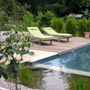 Gartenliegen auf Holzdeck am Pool