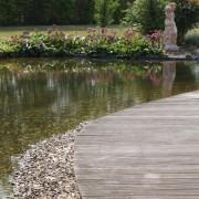 geschwungener Holzsteg direkt am Teich