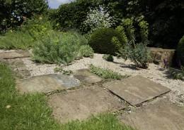 großformatige Trittplatten mit Kies, Wolfsmilch und andere graulaubige Pflanzen