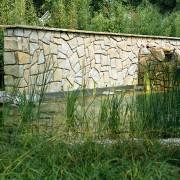 Natursteinmauern als Raumteiler direkt hinter dem Pool ist auch Sichtschutz