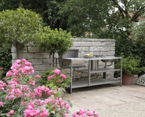 Outdoor-Küche aus Edelstahl vor gartenmauer aus Naturstein