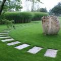 gleichmäßige Tritt-Platten geschwungen im Rasen verlegt