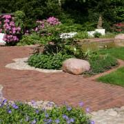 Wasser stilisieren mit wellenförmigen Pflasterlinien und geschwungenen Natursteinflächen