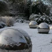 Edelstahlkugeln als Skulptur liegen im sommer und Winter auf dem Rasen